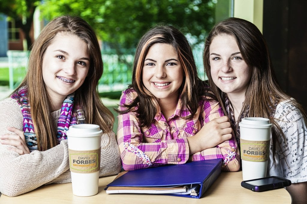 Three smiling girls sitting at a cafe table.