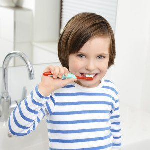 Cute boy brushing teeth.
